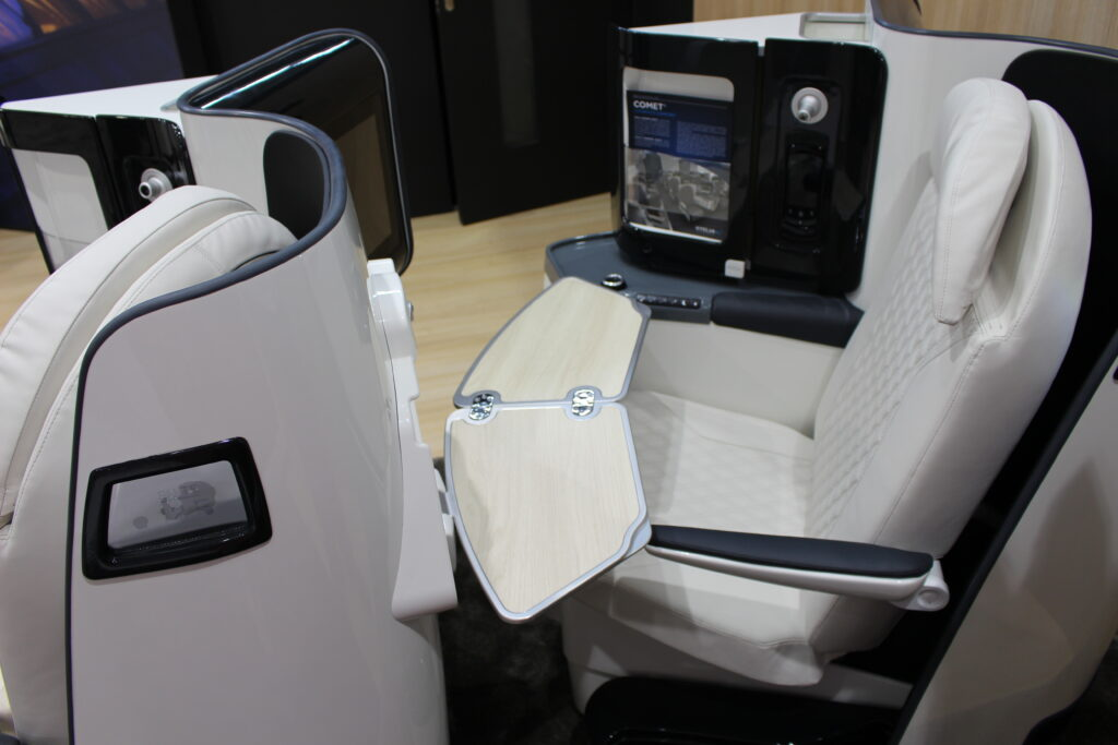 Aircraft herringbone business class seat, Comet, is shown in grey with black trim on the show floor.