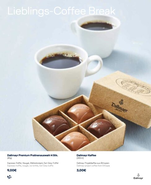A box of four chocolates and two cups of coffee displayed on a white table.