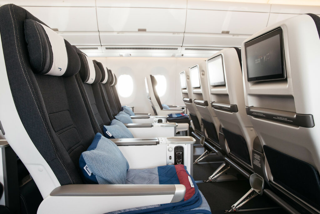 British Airways' Premium Economy seats on an aircraft. Seats are grey with white details and seatback IFE.