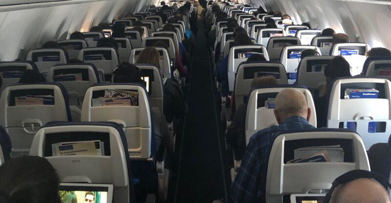 Rows of seats onboard a 737 with passengers using their devices