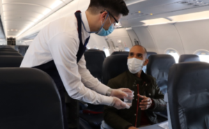 LATAM male flight attendant handing a glass of water to a male passenger. Both are wearing masks.