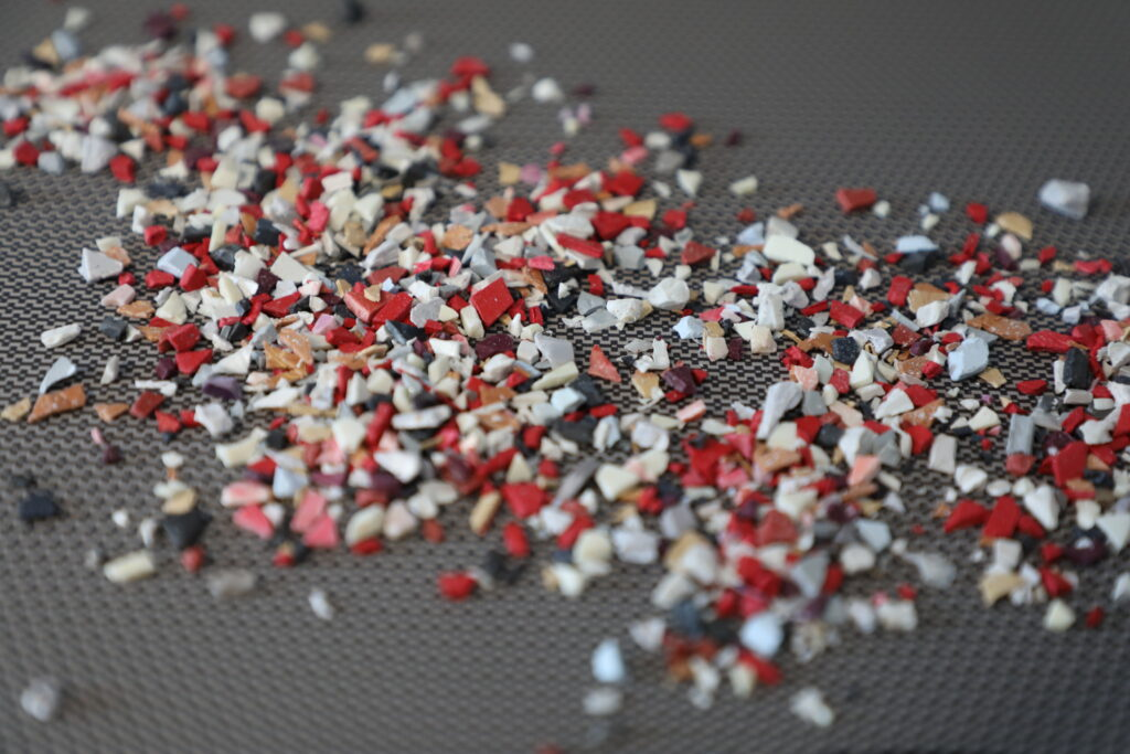 Pieces of diced up thermoplastics bits all over a grey surface.