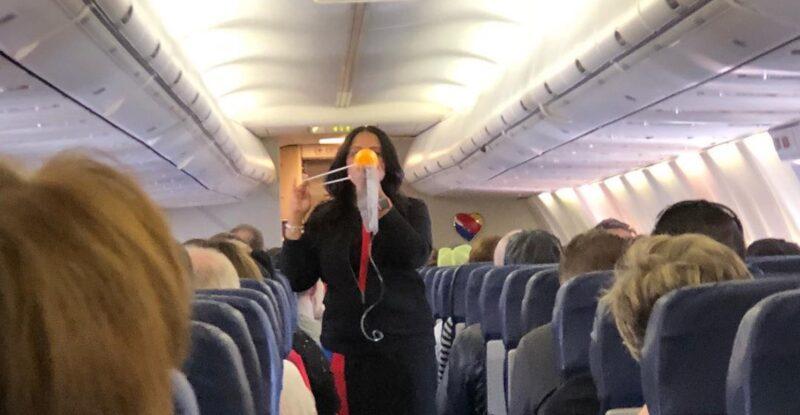 Southwest flight attendant shows passengers how to put on an oxygen mask