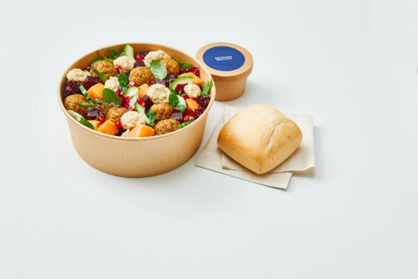 A brown bowl filled with salad and a bun on the side.
