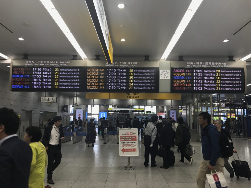 Inside a rail station. Many people walking around. Three large travel information boards above.