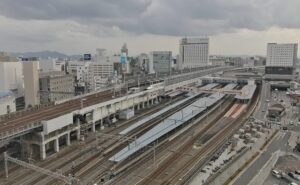 Aerial view of a Japanese city and rail tracks on a cloudy day.