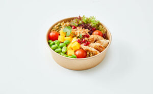 A medium sized bowl full of assorted veggies and chicken.