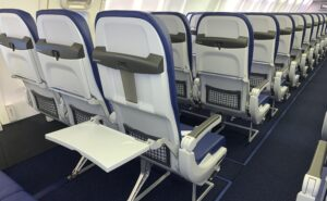 Aircraft interior image of Recaro seats in blue with grey thermoplastics used for the seatbacks and tray tables.