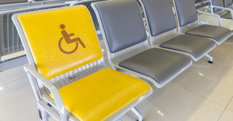 An airport seat designated for a PRM; it is yellow and shows a wheelchair symbol