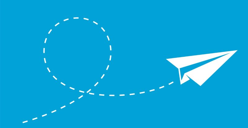 White paper airplane with white dotted line following it on a blue background.