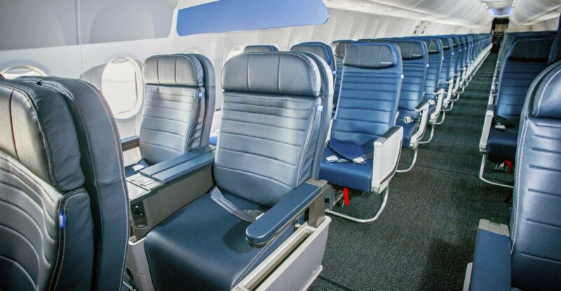 United Airlines Boeing 737 MAX cabin interior showing various seat accommodations in blues and greys. View is front down the aisle with lots of light.
