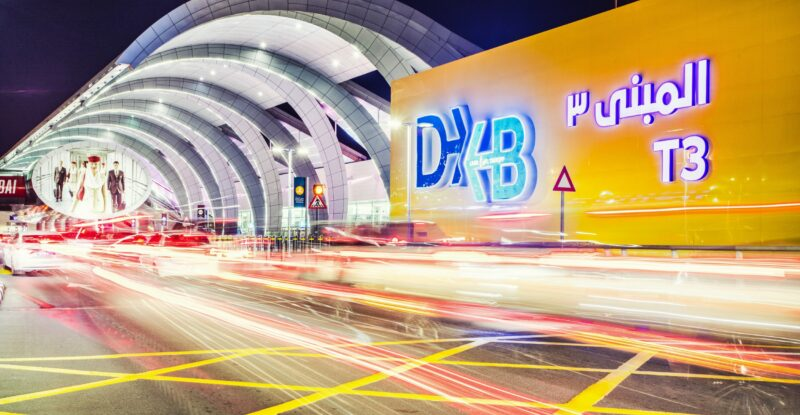Dubai Airport Terminal 3 in the UAE. The airport is a bright yellow with multiple arches coming out from the side of it.