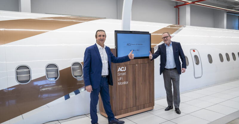 Two men in business suits giving a thumbs up in front of the new ACJ Smart LiFi Monitor. ACJ in the backdrop.