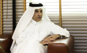 Chairman of the oneworld Governing Board, His Excellency Mr Akbar Al Baker sitting an a large brown chair.