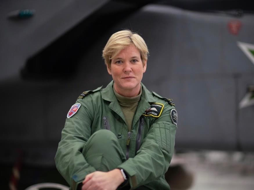 Mandy Hickson in her flight suit, sitting in front of the Tornado GR4, smiling,