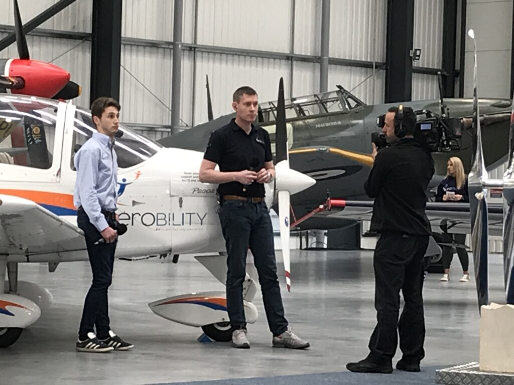 Aerobility aviation activities officer, Harvey Matthewson, at left, prepares to speak live to camera, alongside the charity's Technam