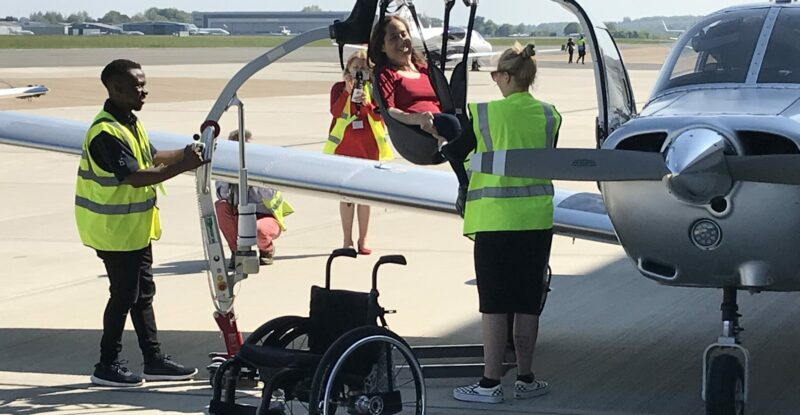 A woman is being hoisted into the aircraft via a sling device.