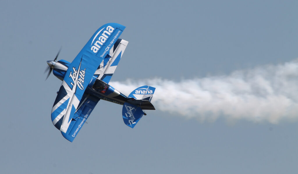 The 'Jet Pitts' aircraft in-flight. Blue and white livery against a blue sky.