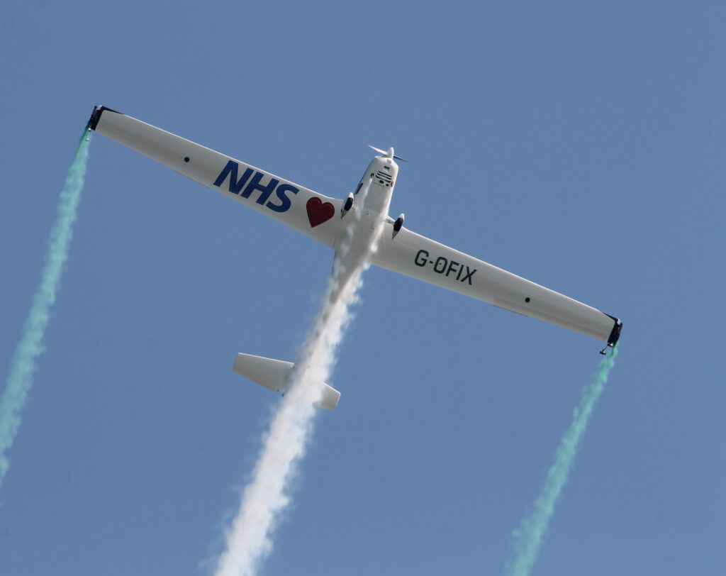 The Grob 109 in-flight against a clear blue sky.