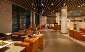 Lufthansa's First Class lounge at Frankfurt Airport. A variety of brown leather seating, large pillars, with wood beams as the ceiling.
