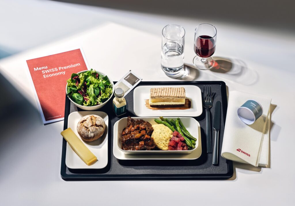 SWISS Premium Economy Class meal on a tray displayed with a menu and two glasses. One with wine and one with water.