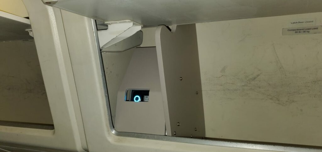 An open overhead bin up close. showing the AirFi box on.