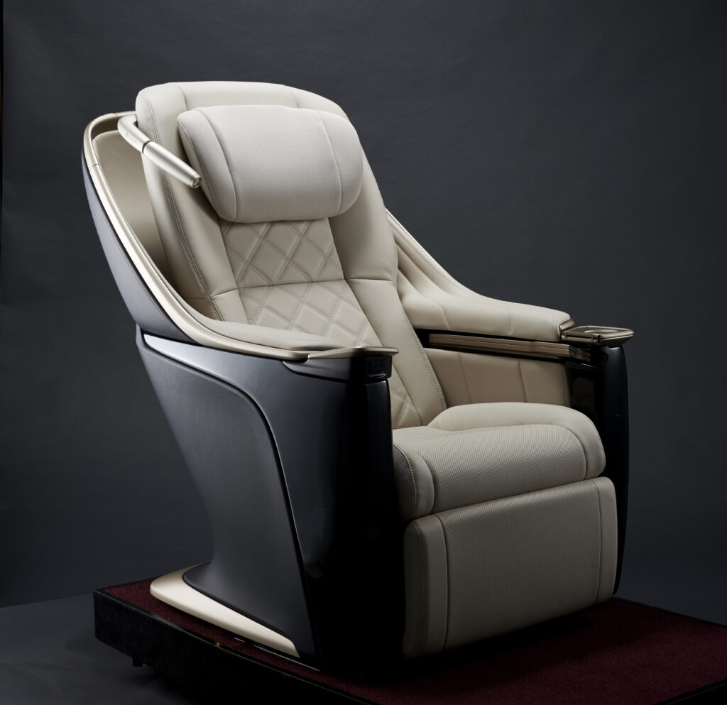 Toyota Boshoku Gran Class seat up close on a black and grey backdrop. Set is all white with a black casing.
