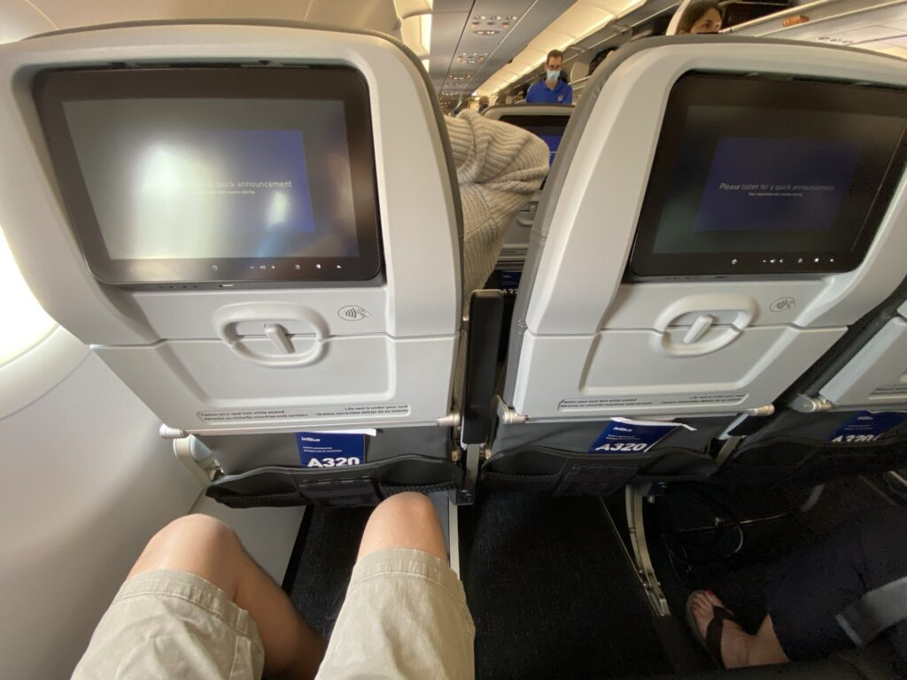JetBlue A320 interior. This is a view of the back of the seat also showing a man's knees. He has plenty of legroom