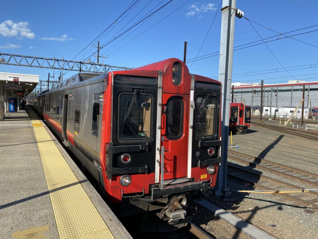 Kawasaki built M8 electric railcar in red and silver pulling up to the boarding station.