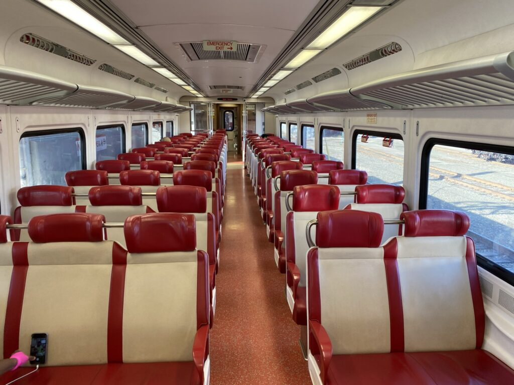 Interior of the Kawasaki built M8 electric railcar. Red trimmed white seats.