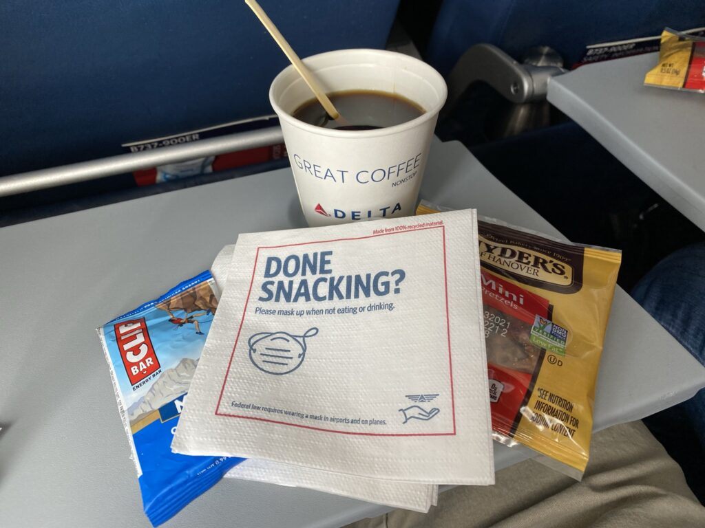 Tray table on the Delta 737 with a coffee, cliff bar and bag of pretzels displayed on it.