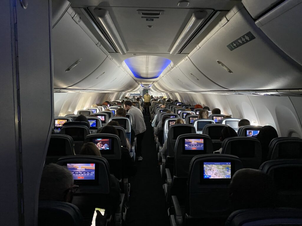 Long view of the Delta 737-900ER cabin with large overhead bins.