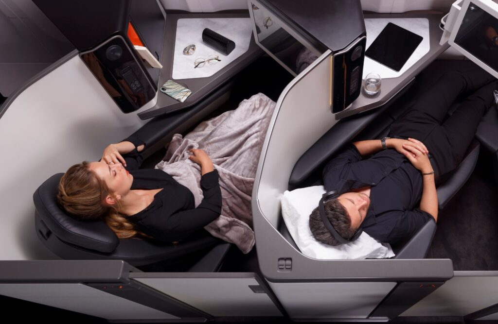 Stelia Business Class seat on an aircraft. A man is lying down in one seat while a woman is sitting up in another.