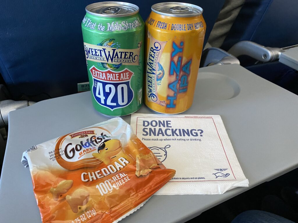 Goldfish crackers snack and two cans of beer on the tray table aboard the 757-200