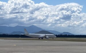 Air Montenegro aircraft on the runway. Large white puffy clouds in the sky and mountains in the distance.