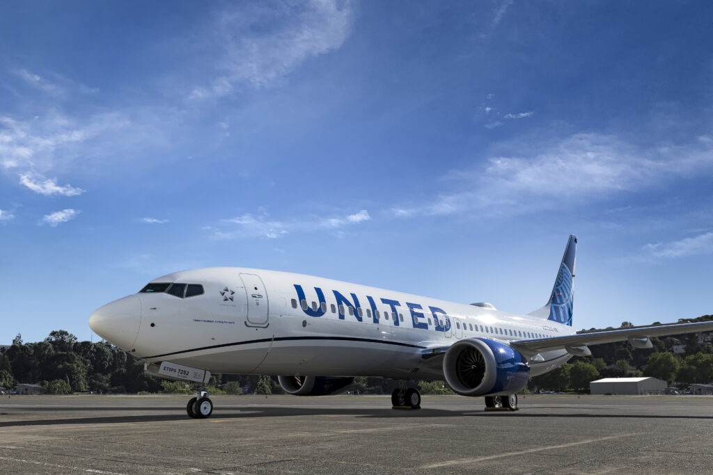 United's Boeing 737 MAX 8, parked, in the carrier's livery, with a blue sky as background