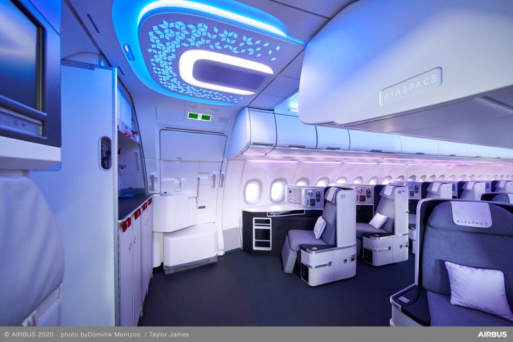 Airbus Airspace Cabin with blue LED lighting design on the ceiling and an open view of the galley and business class seats.