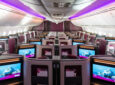 A view of the Qatar 787 Adient Ascent business class seats with purple LED lights decorating the cabin