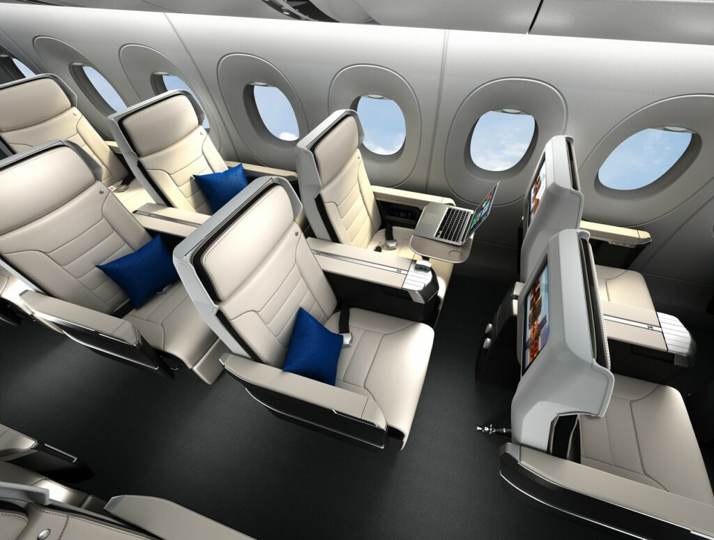 Safran Seats Z600 rendering in an aircraft. All white seats with black trim. Blue pillows on each seat and one seat has a laptop displayed on a tray table