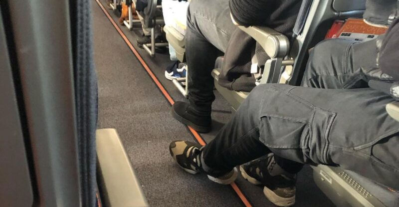 Passengers on board, with their legs stretched into the aisle