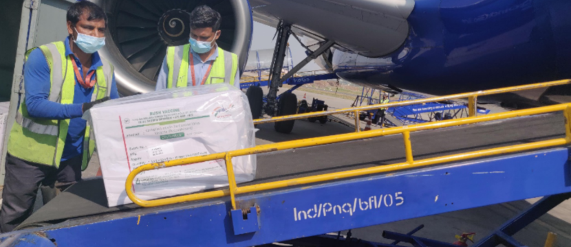 Two men loading a package into the cargo of aircraft.