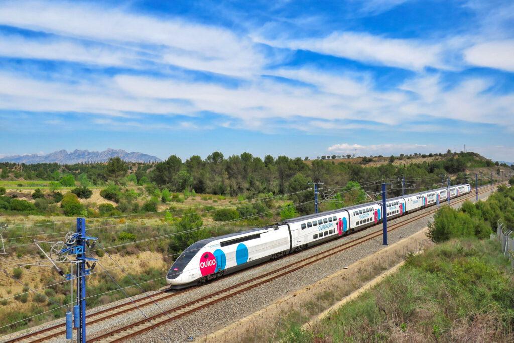 El tren español Oigo se mueve a lo largo de la vía en una pintoresca vista de árboles con un cielo azul brillante.