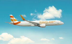 SunClass Airlines Aircraft on flight. Bright blue sky with white puffy clouds in the background.