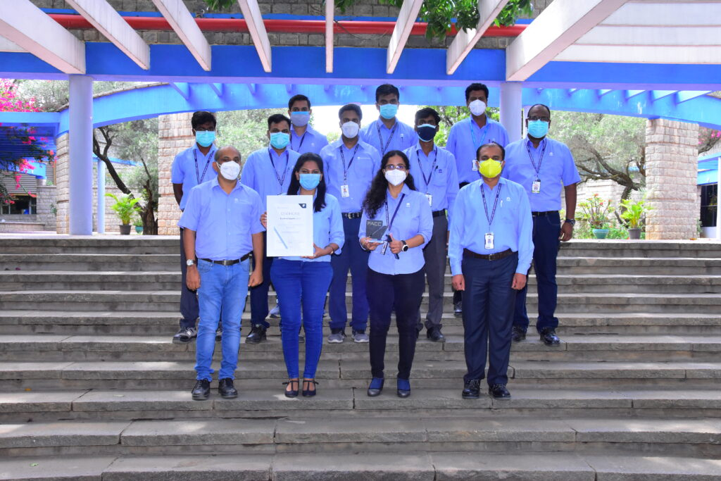 Tata Advanced Systems team members all standing on a set of stairs posing for the photo with the award received. Image: FACC