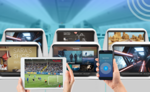 Multiple Thales IFE screens behind a tablet and mobile phone.