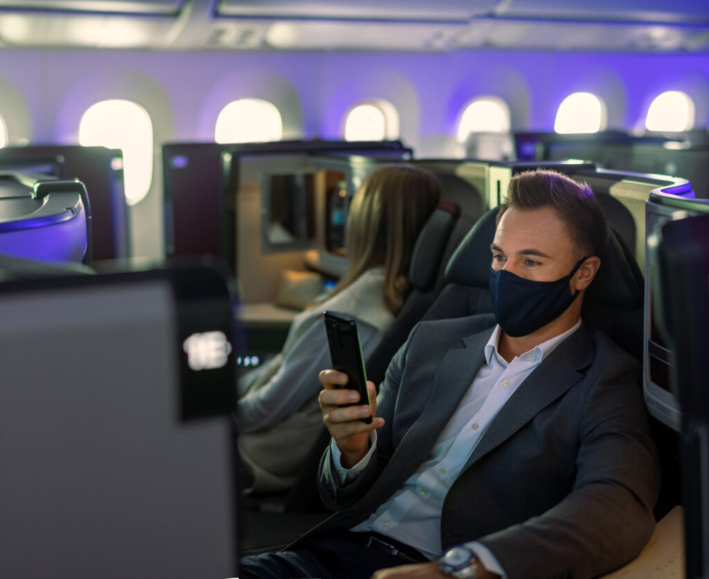 A man sitting in a Qatar Airways aircraft. The man is wearing a mask and looking at his mobile device.