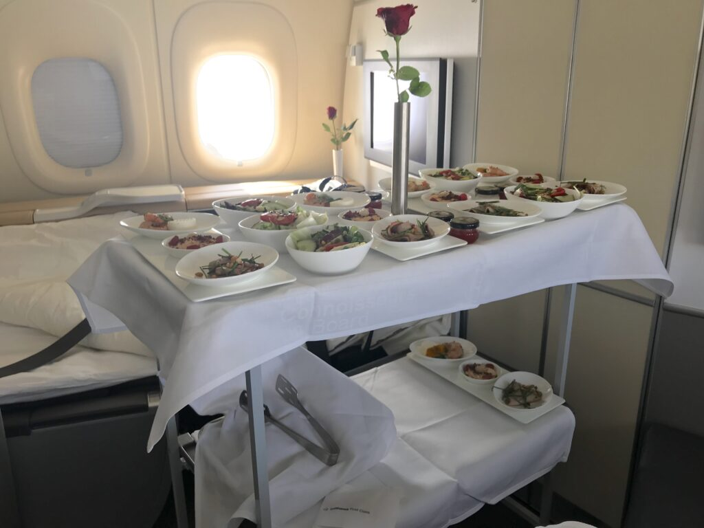 Aircraft trolley with a display of a first course meal in first class. A white cloth covers the two-tiered trolley