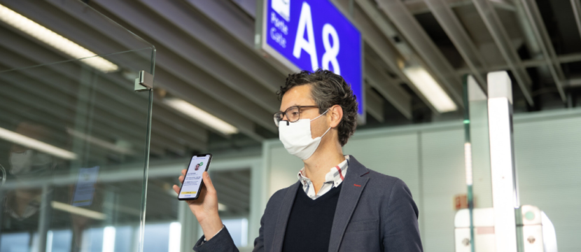 A man shows the IATA Travel Pass to a boarding agent at the airport