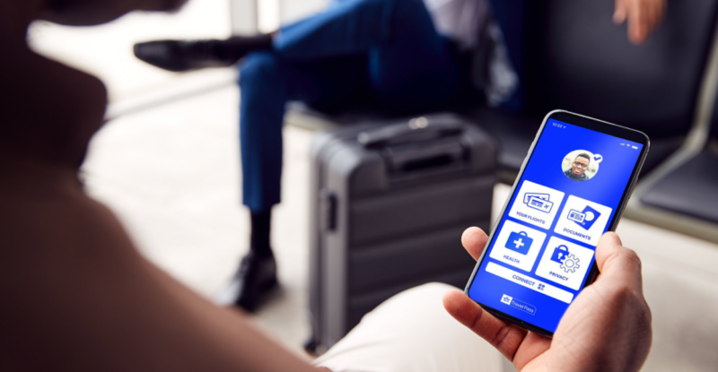A passenger looks down at the IATA Travel Pass app on his mobile phone