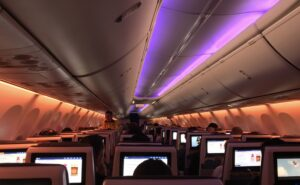 Aircraft interior view from the rear of the aircraft. IFE seatback screens and passenger' heads are visible.